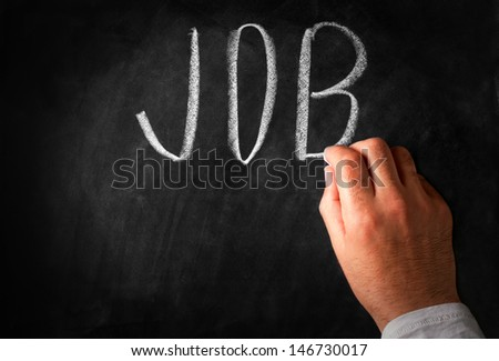 Male hand writing the word Job in capital letters on a black chalkboard with a piece of chalk