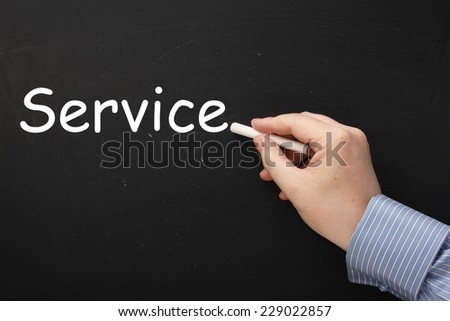 Male hand writing the word Service on a blackboard with white chalk