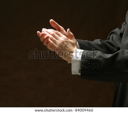 Male hands applauding on black background