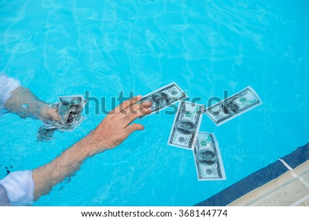 Male hands catching money in the swimming pool