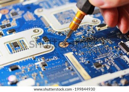 Male hands close up fixing microchip with a screwdriver - stock photo