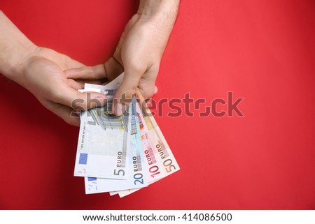 Male hands counting euro banknotes on red background