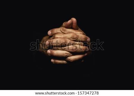 Male hands crossed for prayer in dark - stock photo