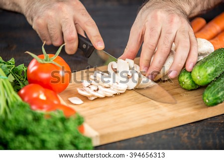 Male hands cutting vegetables for salad