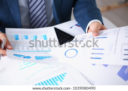 Male hands hold documents laptop with financial