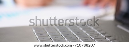 Male hands hold documents laptop with financial statistics at office workspace closeup. White collar check money papers, stock exchange market, internal Revenue Service inspector, earning list concept