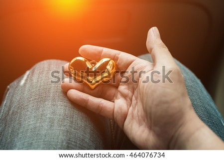 male hands hold gold heart shape. love concept