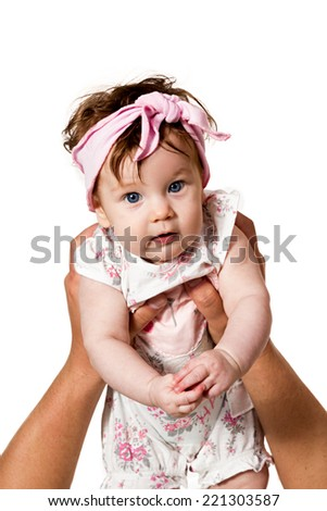 Male hands holding a baby girl with blue eyes who is looking at the camera isolated on white background
