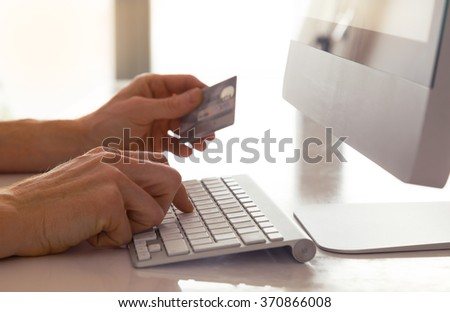 Male hands holding a credit card at a keyboard during online shopping. - stock photo