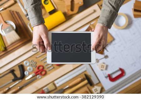 Male hands holding a digital tablet, work table with tools and project on background, home renovation and do it yourself concept - stock photo