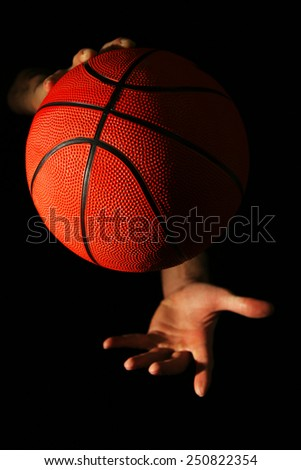 Male hands holding basketball ball on dark background