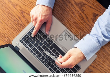 Male hands holding credit card and pressing enter key, top view - online shopping