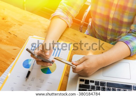 male hands holding credit card typing numbers on mobile phone and computer keyboard while sitting at home at the wooden table,shopping online security,selective focus, morning sun light, vintage color - stock photo