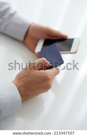 Male hands holding credit card when paying mobile phone
