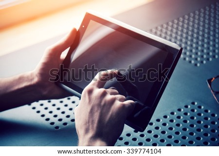 male hands holding digital tablet touching with finger - stock photo