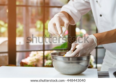 Male hands holding eggshell. White eggshell and bowl. Chef breaks fresh egg. Clean product for delicious meal.