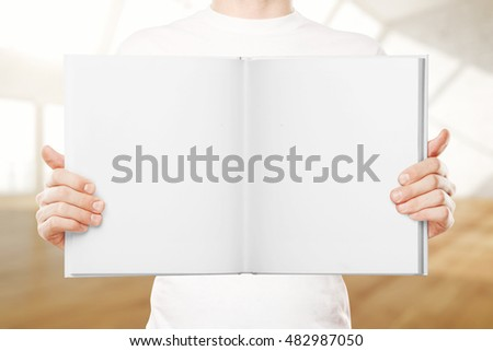 Male hands holding empty open book on blurry background with daylight. Mock up, 3D Rendering