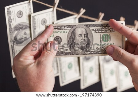 Male Hands Holding Hundred Dollar Bills with Several Hanging From a Clothesline on a Dark Background. - stock photo