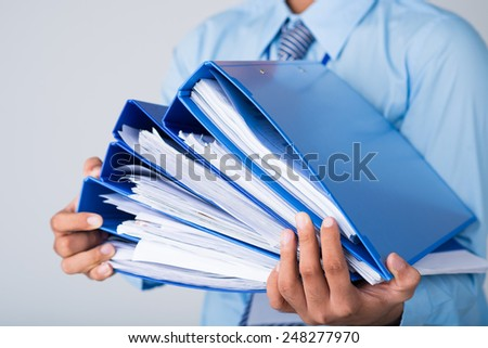 Male hands holding pile of binders - stock photo