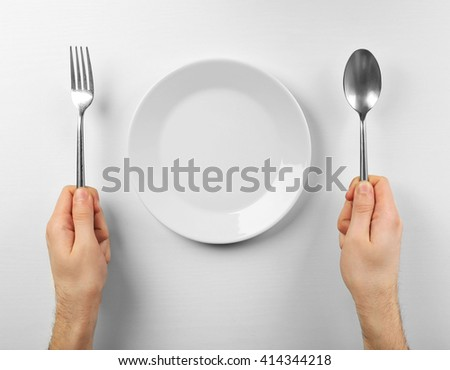 Male hands holding silver cutlery near plate, isolated on white - stock photo