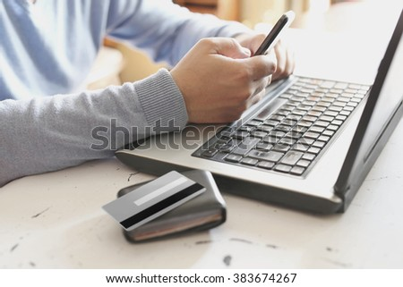 Male hands holding smart phone in front of laptop computer