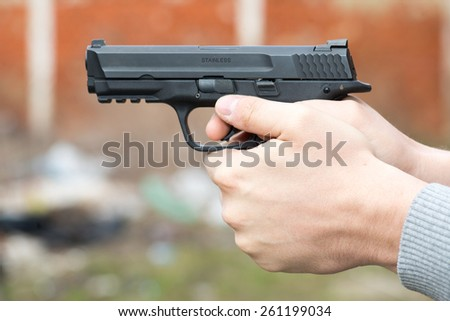 Male hands holding the gun and aiming - stock photo