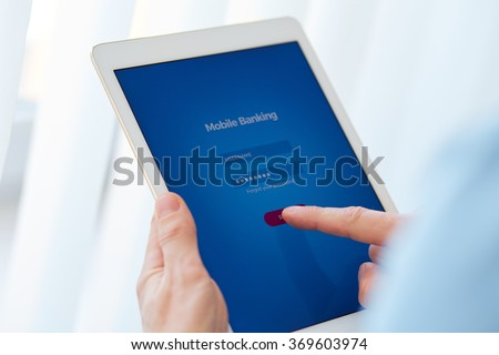 Male hands holds a tablet with online banking, login page on the touch screen