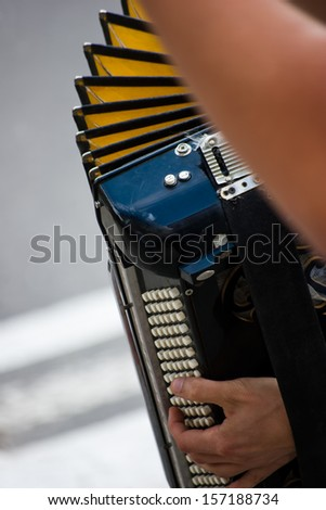 male hands manipulating the accordion - stock photo