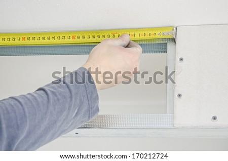 Male hands measuring gypsum plasterboard frame - stock photo