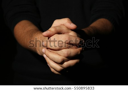 Male hands on a black background