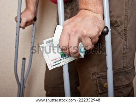 Male hands on crutches with money on wall background. - stock photo