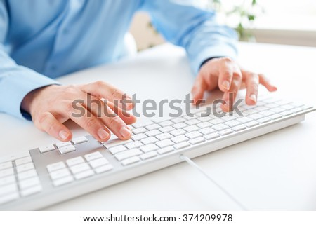 Male hands or men office worker typing on the keyboard - stock photo