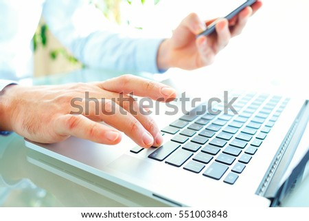 Male hands or men office worker typing on the keyboard and using smartphone