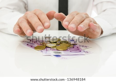 Male hands over Euro coins and banknotes. Money concept. - stock photo