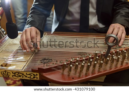 Male Hands Playing Arabian Qanon Musical Instrument During a Symphony - stock photo