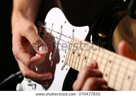 Male hands playing electric guitar with plectrum closeup photo. Learning musical instrument, music shop or school, blues bar or rock cafe, having fun enjoying hobby concept - stock photo