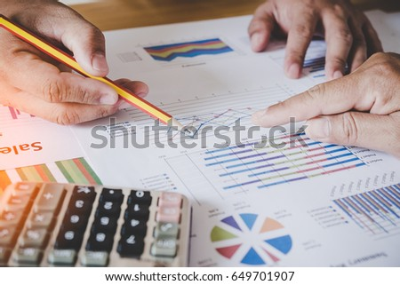 male hands pointing at turnover graph while discussing it on wooden desk in office. group support concept.