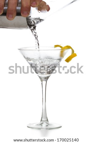 male hands pouring a vodka martini in to a chilled glass with a lemon twist - stock photo