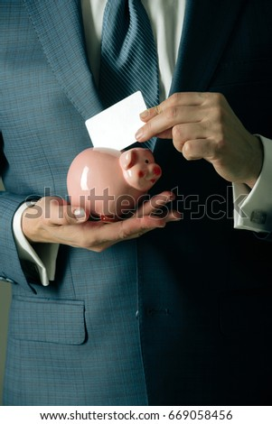 Male Hands Putting Blank Business Card In Piggy Bank For Saving On Grey  Background. Stylish