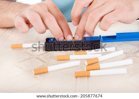 Male hands rolling a cigarette using rollings or a sticky paper with fresh ground tobacco - stock photo