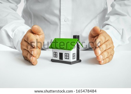 Male hands saving small house. Real property or insurance concept - stock photo