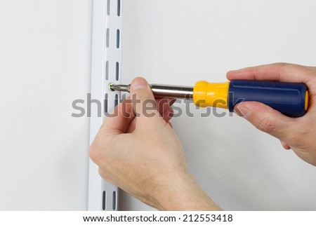 Male hands screwing wood screw into support bracket on wall with manual hand tool screwdriver  - stock photo