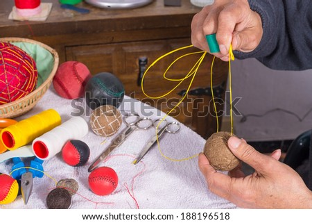 Male hands  sewing traditional jai alai  balls - stock photo