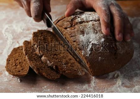 Male hands slicing fresh bread - stock photo
