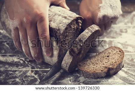 Male hands slicing home-made bread - stock photo