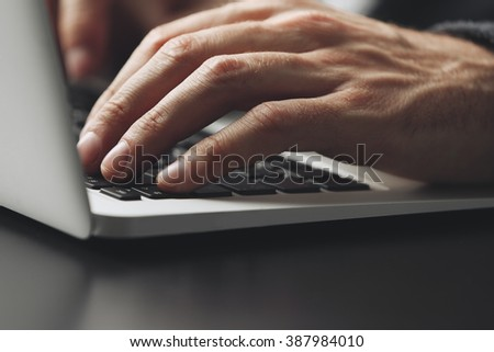 Male hands typing on laptop keyboard at table closeup - stock photo