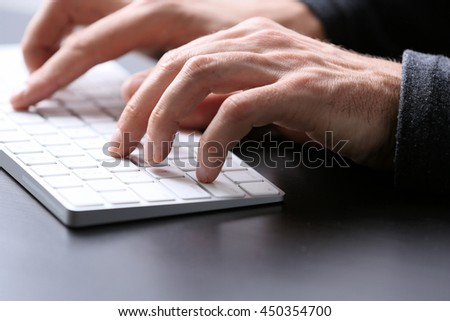 Male hands typing on wireless keyboard at table closeup - stock photo