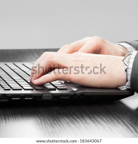 Male hands typing something on laptop - 1 to 1 ratio
