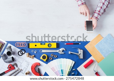 Male hands using a mobile phone next to plumbing work tools, tiles and swatches, online booking and home plumbing service - stock photo