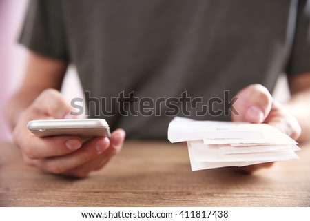 Male hands using calculator apps at the table - stock photo
